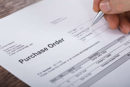 Close-up van een persoon Hand Vullen een bestelbon wordt op houten bureau