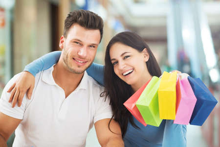 Portrait Of A Smiling Couple With A Colorful Shopping Bag In The Shopping Mall photo