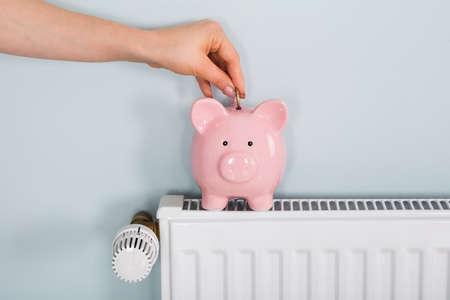 Gros plan, femme, main, insertion, monnaie, Piggybank, radiateur, maison