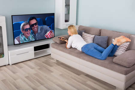changing channels: Woman Lying On Couch Watching Movie On TV In Living Room At Home