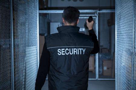 uno: Vista trasera de un guardia de seguridad de pie en el almacén de la explotación agrícola de la linterna