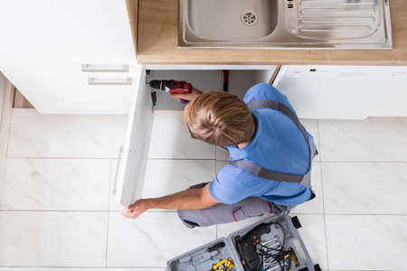 High Angle View Of Man In Overall Repairing Cabinet With Wireless Screwdriver