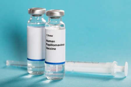 Vacuna contra el virus del papiloma humano en botellas con fondo Jeringa sobre la turquesa