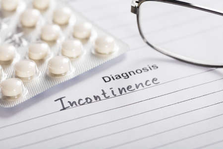 incontinence: Close-up Of Drug And Glasses On Piece Of Paper With Text Diagnosis Incontinence Stock Photo