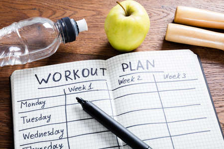 High Angle View Of A Workout Plan In Notebook At Wooden Desk Imagens - 72006561