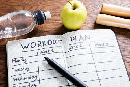 Vista de alto ângulo de um plano de treino no caderno na mesa de madeira