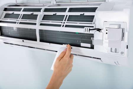 Close-up d'une personne à la main Nettoyage Air Conditioner Avec Vaporisateur At Home Banque d'images