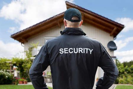 家の外に立っている男性警備員の後姿