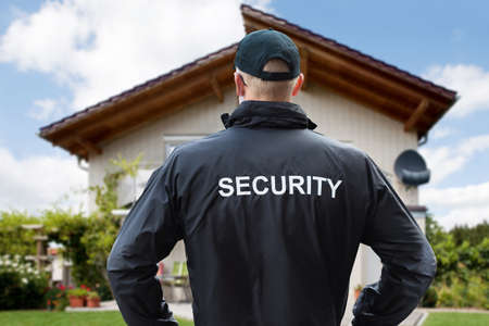Rear View Of A Male Security Guard Standing Outside The House