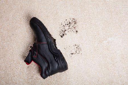 Vista De Alto ángulo De Un Par De Zapatos Con Barro En El Piso De La Alfombra