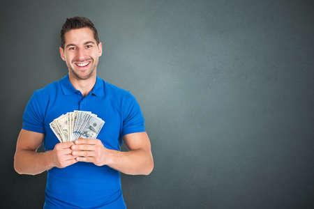 cash money: Joven feliz Hombre que sostiene el aventado moneda nota en el fondo gris