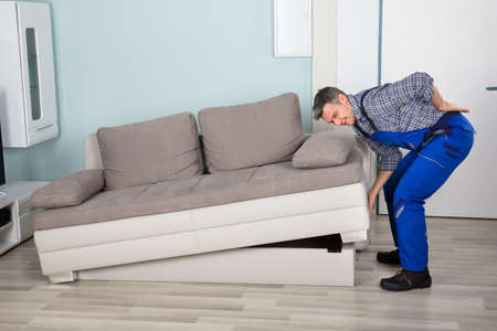effort: Male Worker Suffering From Back Pain While Lifting Sofa In Living Room At Home