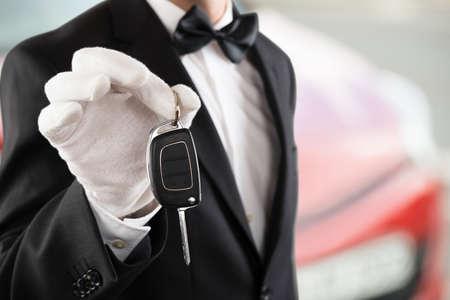 車の外の車のキーを保持している係員少年のクローズ アップ 写真素材