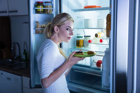 secretly: Suspicious Woman Taking Sweet Food Secretly From Fridge In The Kitchen