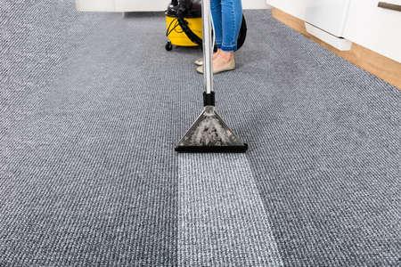 掃除機でのカーペットの掃除用務員のクローズ アップ 写真素材