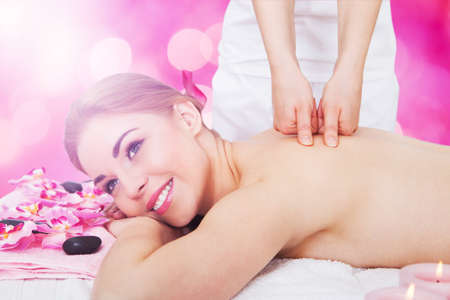 Close-up Of A Young Happy Woman Receiving Back Massage At Beauty Spa photo