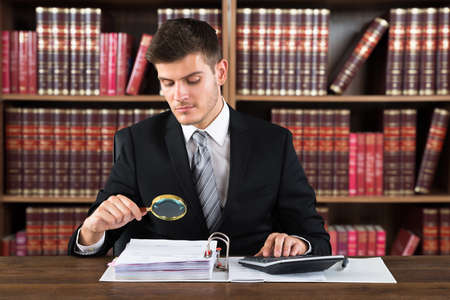 account executive: Male Lawyer Auditor Bills Using Magnifying Glass And Calculator Stock Photo