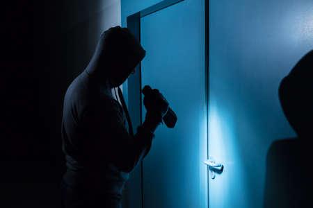 intruding: Burglar Holding Flashlight Outside The Door Before Breaking In