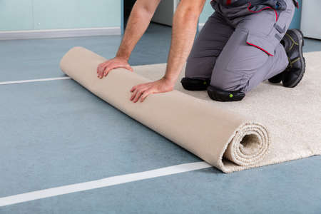 close fitting: Close-up Of Workers Hands Rolling Carpet At Home