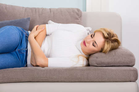abdominal wall: Young Unhappy Woman Lying On Sofa Suffering From Stomach Ache At Home