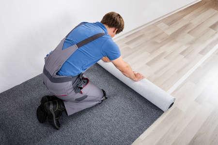 Junge Männliche Handwerker Rolling Teppich Auf Boden Zu Hause