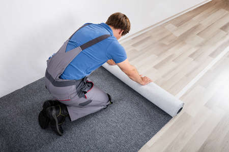 overalls: Young Male Handyman Rolling Carpet On Floor At Home Stock Photo