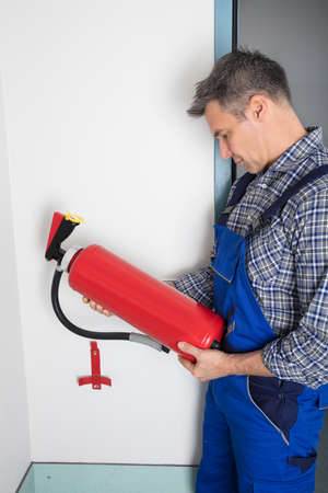 Male Professional Checking The Condition Of A Fire Extinguisher Stock Photo