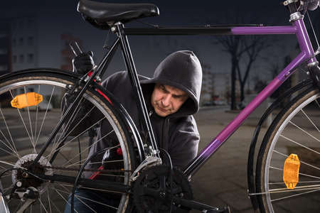 Thief Using With Long Pliers To Break The Bicycle Lock
