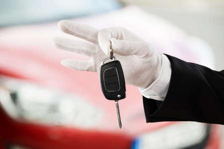 Gros plan d'une main de garçon de valet tenant la clé de voiture à l'extérieur de la voiture Banque d'images