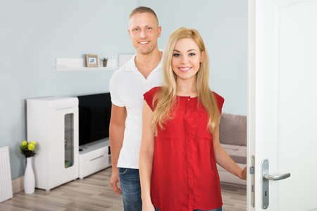 tv wall: Portrait Of A Young Happy Couple Standing Near Door Of The House