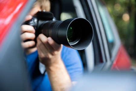 一眼レフ カメラで撮影の車の中に座っている私立探偵