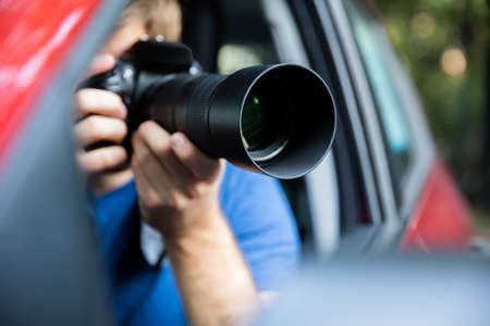 Private Detective Sitting Inside Car Photographing With SLR Camera Фото со стока