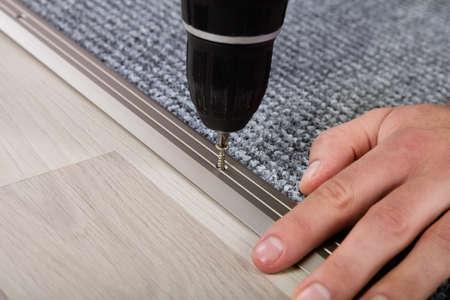 人の手の無線ドライバーを使用して床にカーペットをインストールします。 写真素材