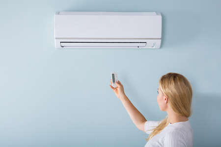 Young Woman Operating Air Conditioner With Remote Controller At Home Banco de Imagens
