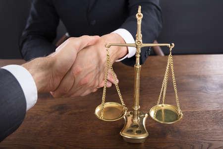 Close-up van een rechter en cliënt die handen dichtbij Rechtvaardigheidsschaal schudden op Houten Schaal Stockfoto - 72570088