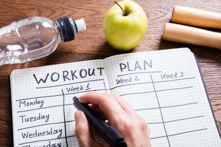 High Angle oog op een Workout Plan In notitieboekje bij houten bureau