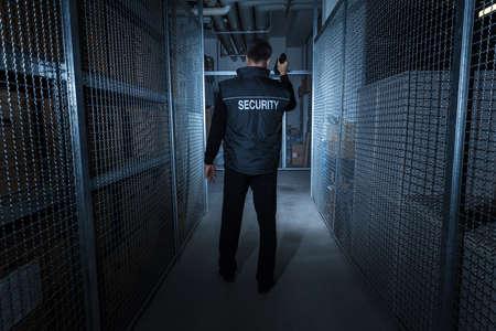 Vista posteriore di una guardia di sicurezza che si leva in piedi nel magazzino che tiene la torcia elettrica Archivio Fotografico