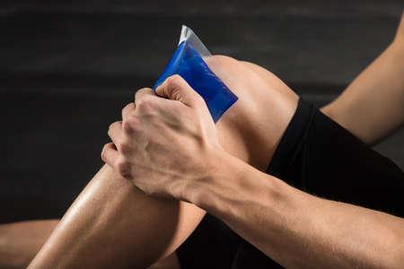 artrosis: Primer plano de una persona aplicando bolsa de hielo sobre una rodilla lesionada en el gimnasio Foto de archivo