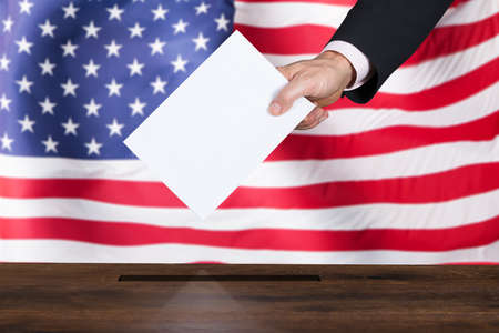 Close-up Of A Businessperson Inserting Ballot In Box In Front Of American Flag Stock Photo