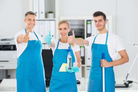 Portrait Of Smiling Janitors Holding Cleaning Equipments Showing Thumbs Up In Office