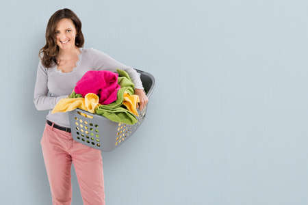 chores: Portrait Of A Happy Woman Carrying Laundry Basket On Colored Background