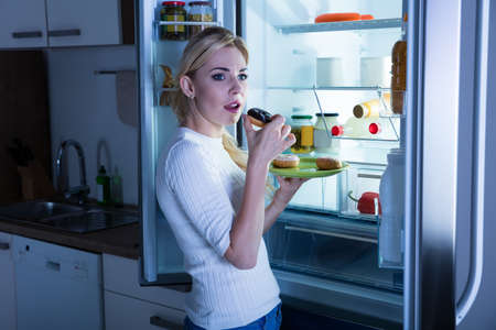 secretly: Young Woman Standing In The Kitchen Eating Donut Secretly From Fridge Stock Photo