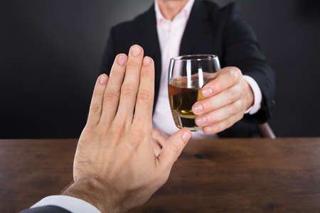 alcohols: Businessman Hand Rejecting A Glass Of Whiskey Offered By Businessperson