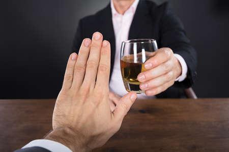Uomo d'affari a mano rifiutare un bicchiere di whisky offerta da Businessperson