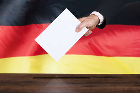 Close-up Of A Person Putting Vote In A Ballot Box In Front Of German Flag
