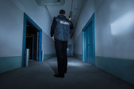 security guard: Mature Male Security Guard With Flashlight Standing In Corridor Of The Building