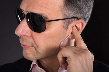 Close-up Of A Male Security Guard Listening To Earpiece On Gray Background Stock Photo