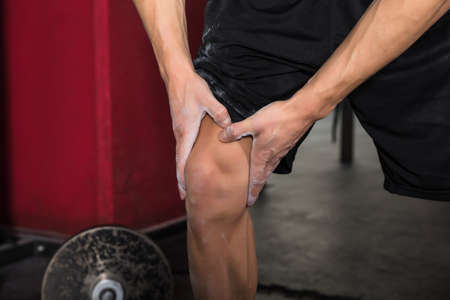strengthen hand: Close-up Of A Man Suffering From Knee Pain After Exercise In The Gym Stock Photo