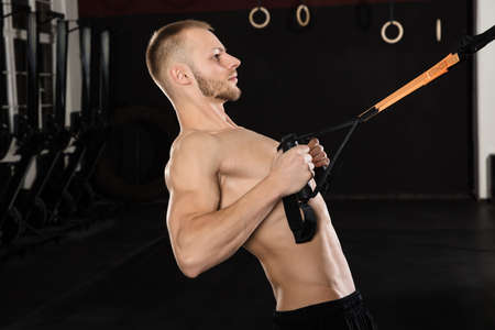 Close-up Of A Young Male Athlete Exercising With Suspension Trainer In The Gym