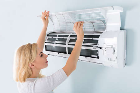 A Young Woman Cleaning Air Conditioning System At Home